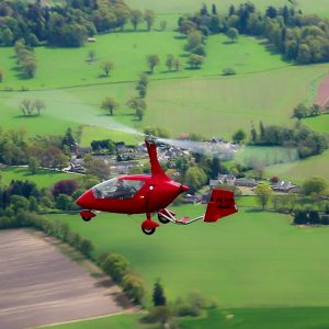 red gyrocopter in the air with pilot and passenger