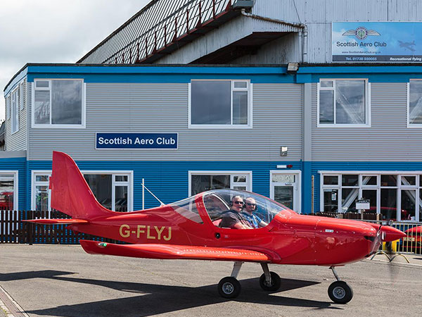 Red fixed wing microlight in front of the Scottish Aero Club