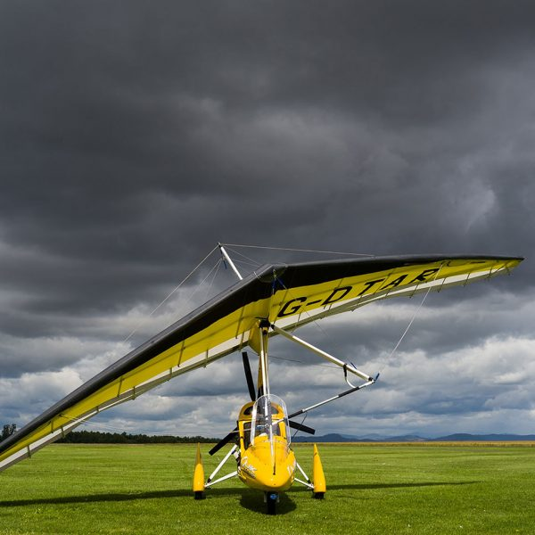 Flexwing microlight on the grass with dark clouds above