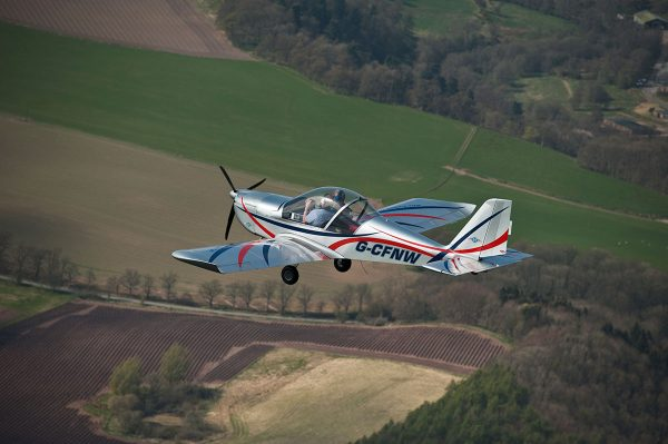 Fixed wing microlight in the air over fields