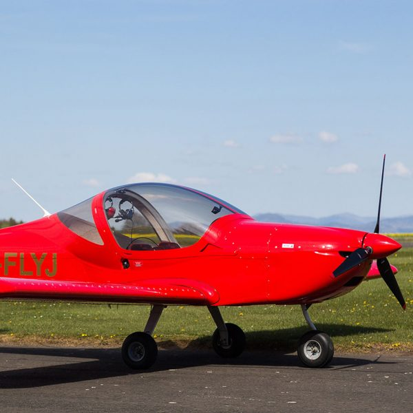 Red fixed wing microlight on the runway