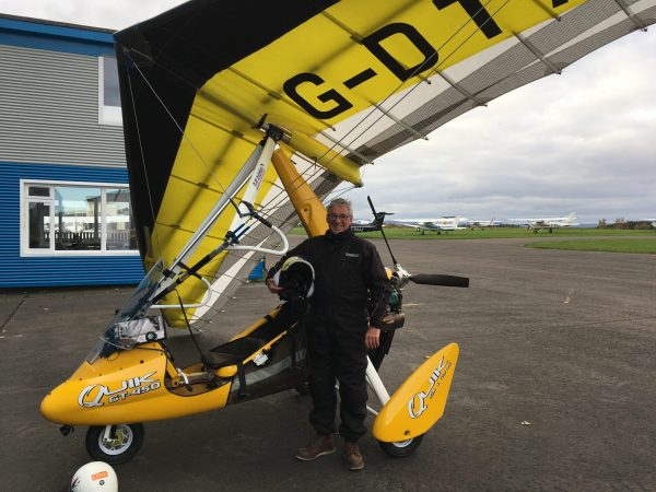 Man standing in front of flexwing microlight